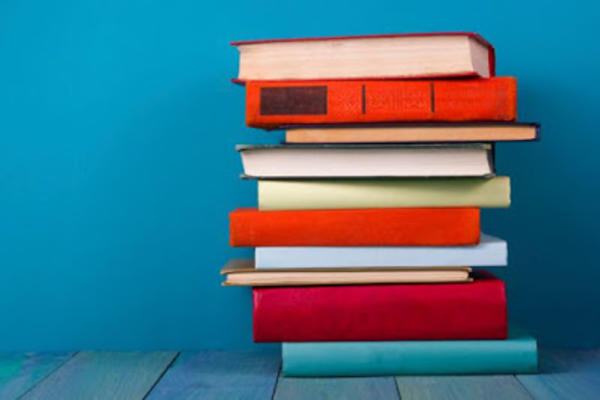 pile of books against blue background i stock
